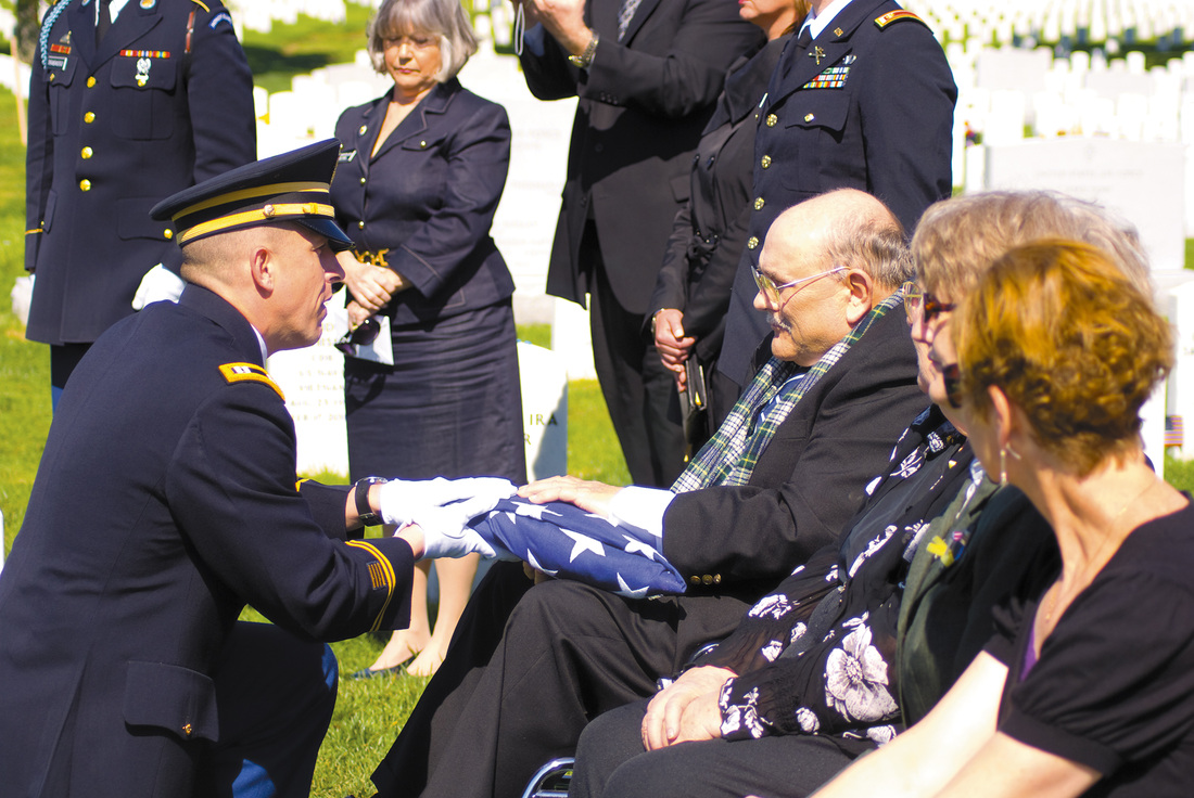 Chaplain Kelly O'Leary presents the flag that covered <br> Rip Winkler's coffin to his son, Lance.
